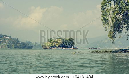 Small island with trees surrounding a monastery. Taal Barahi Temple on Lake Phewa, Pokhara in Nepal.