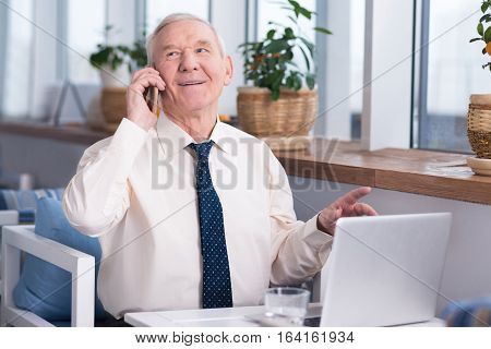 I can agree to that. Emotional handsome elderly man talking with his colleague on the phone while sitting in a restaurant and working on his laptop