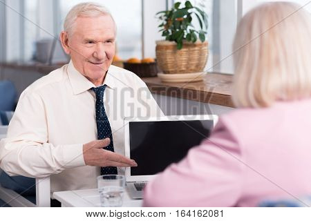 This is tempting. Enthusiastic nice experienced businessman demonstrating his work on his laptop to his business partner while sitting at the table in a cafe
