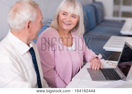 I want to show you my project. Good looking elderly man and enthusiastic grey haired woman being engaged in negotiations concerning their common business while sitting at the table and using a laptop