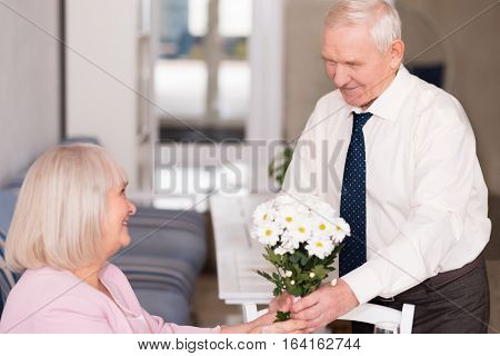 Nice present. Pleasant good looking suave man giving his lady flowers to celebrate their love while she sitting at the table with a glass of champagne on it