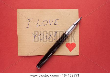 pencil red heart and confession letter on craft background
