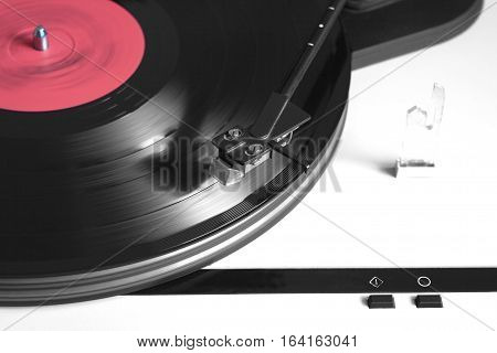 Record player in silver case with black tonearm playing a vinyl record with red label. Horizontal photo top view closeup