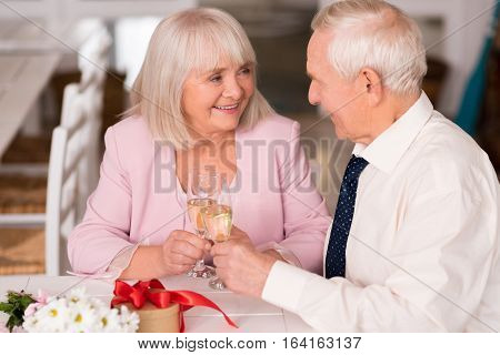 One more toast. Radiant happy lady and her fine companion holding glasses of champagne while talking to each other at the table in a cafe