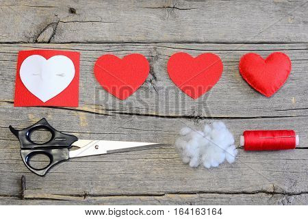 Red felt heart, cut felt parts in shape of a heart, paper pattern, scissors, thread, needle on a wooden table. Felt heart craft for Valentine's day gifts and decorations. Instruction. Top view