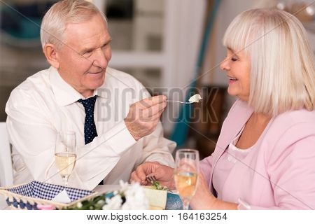 Take another bite. Gallant grey haired senior man feeding his attractive companion with cake during their celebration in a restaurant