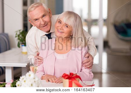 Look at the camera. Graceful cheery senior couple posing for a picture capturing an important and unforgettable evening in their life