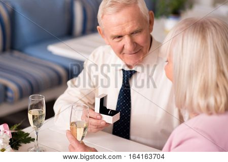 My heart is ours. Charming gallant senior man asking his lady marrying him while sitting at the table in a restaurant celebrating their anniversary