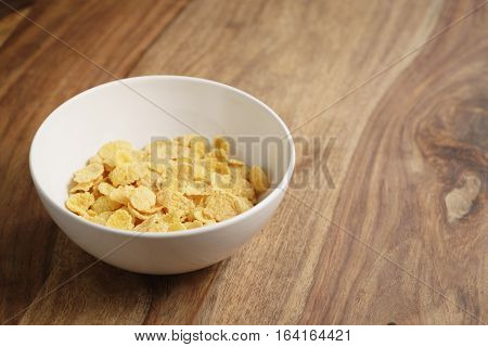 dry corn flakes in white bowl on wood table, copy space on right side