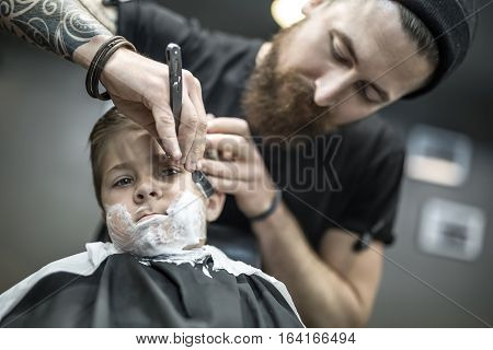 Small kid with a shaving foam on the face in the barbershop. He wears a black salon cape. Bearded barber with a tattoo is shaving boy's face with the help of the straight razor. Low aperture photo.