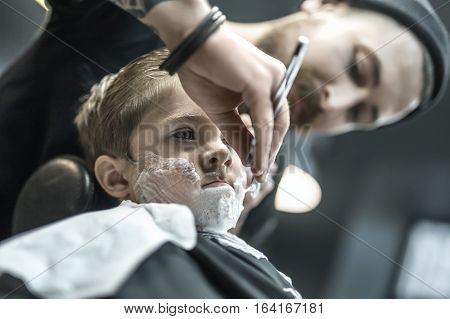 Brutal kid with a shaving foam on the face in the barbershop. He wears a black salon cape. Bearded barber with a tattoo is shaving boy's face with the help of the straight razor. Low aperture photo.