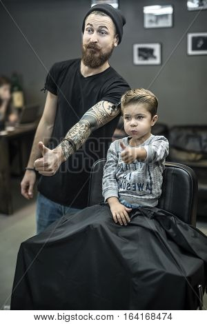 Happy small kid with the new hairstyle and the bearded tattooed barber are doing grimaces and showing the thumbs up sign. Boy wears a gray sweatshirt. Hairdresser wears a black T-shirt and cap, jeans.