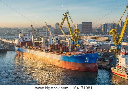 Casablanca Morocco - December 8 2016: Cargo vessel Discovery Bay (Bulk Carrier) early in the morning at dawn in the seaport of Casablanca Morocco. The scene with harbor cranes and ships in the port.