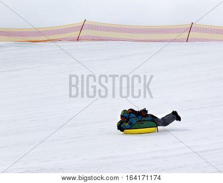 Snow tubing at ski resort in gray day