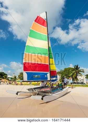 Bridgetown Barbados - December 18 2016: Brownes beach at ocean coast with people and colorful sail on a catamaran at sunny day in Bridgetown Barbados.