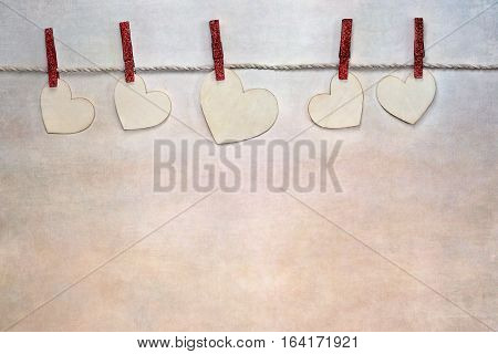 Wooden love Valentine's hearts clipped to cord by red clothes pins over textured background with copy space available.