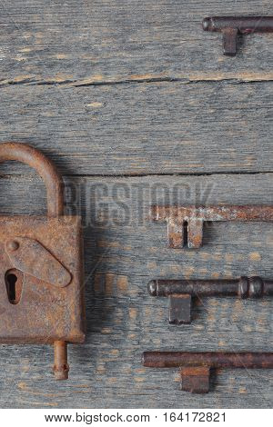 Old padlock and keys lie on a wooden board