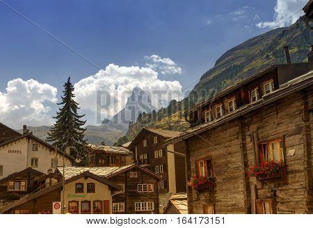 Matterhorn surrounded with clouds in front of Zermatt village houses by day, Zermatt, Switzerland
