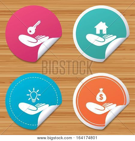Round stickers or website banners. Helping hands icons. Financial money savings insurance symbol. Home house or real estate and lamp, key signs. Circle badges with bended corner. Vector