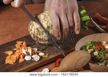 Chef chopping vegetables on kitchen board. Vegetables for conservations