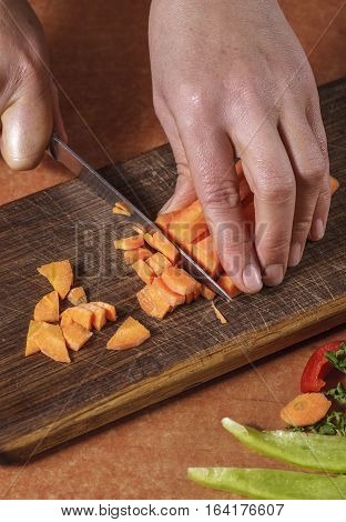 Chef chopping vegetables on kitchen board. Vegetables for conservation