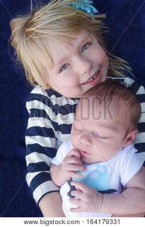 siblings big sister holding newborn baby brother