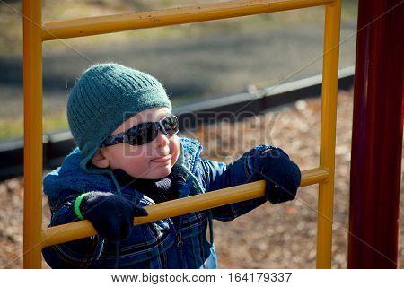 adorable toddler boy climbing ladder at park
