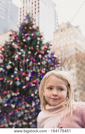 Beautiful school age girl standing in front of giant Christmas tree in Bryant Park
