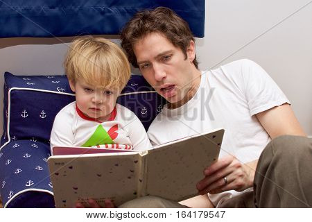 father and toddler son reading bedtime story
