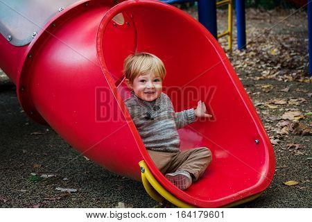 Adorable toddler boy sitting at bottom of slide at park during fall autumn season