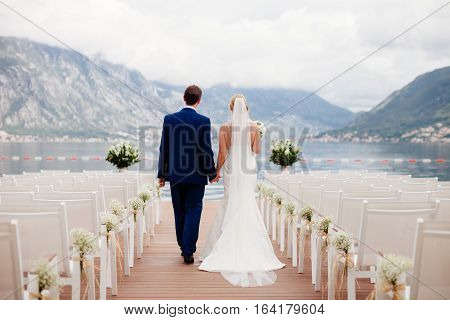 wedding couple at wedding ceremony back view. Mountains and sea background in Montenegro