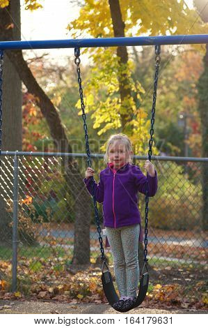 Adorable school age girl standing on swing in park in fall autumn season