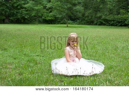 beautiful young school age girl wearing dress smelling flowers on field