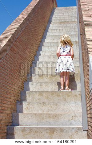young school age girl child standing on steps of medieval wall in Girona Spain