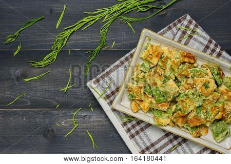 Acacia Pennata Omelette on a plate with tablecloth on wooden table Thai local food
