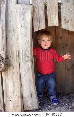 Adorable toddler boy playing in playhouse doorway outside on playground