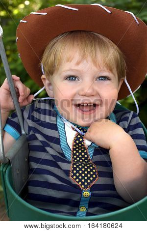 Adorable toddler boy wearing cowboy hat and sitting in bucket swing