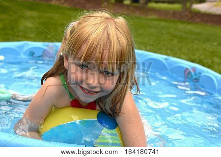 Adorable school age girl playing in plastic kid pool outside in summertime