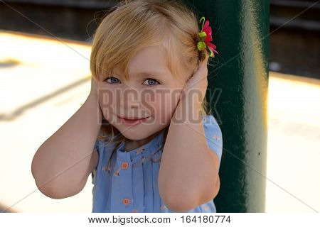 Adorable school age girl holding ears from loud noise at train station