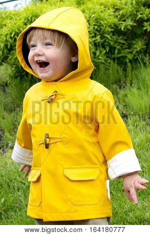 Adorable toddler boy smiling wearing raincoat outdoors
