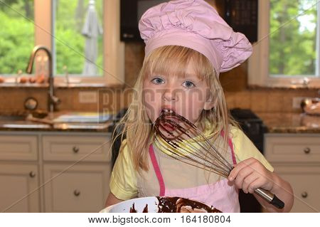 Adorable school age girl wearing chef hat licking chocolate batter of whisk while baking