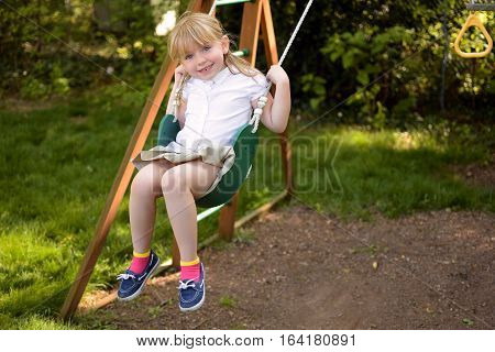 Adorable school age girl outside playing on swing