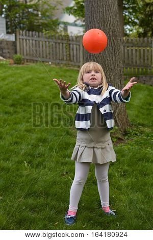 adorable school age girl throwing up basketball during spring season