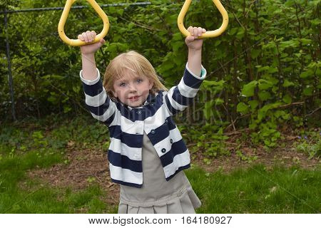 adorable school age girl hanging from playground equipment
