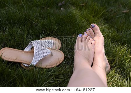 womans feet with sandals relaxing on grass