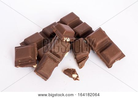 A few cubes of dark chocolate chunks pieces on white background