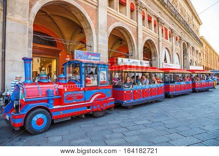 Bologna, Italy - May 28, 2016: Tourist train at side of Palazzo dei Banchi in Piazza Maggiore. San Luca Espress is the tourist line which connects the historic center with the Basilica of San Luca.