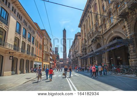 Bologna, Italy - May 28, 2016: People walking in the middle of Via Rizzoli, restricted traffic zone, closed to traffic during the day on Saturday. The two towers, symbol of Bologna, on background.