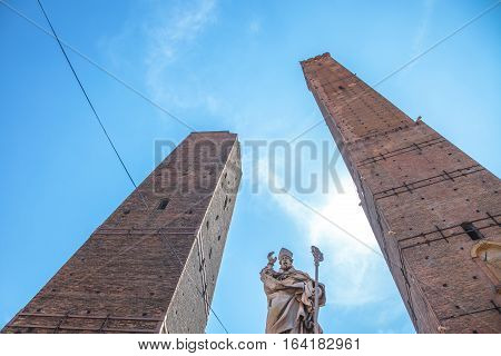 Perspective view of Due Torri or Two Towers: Torre degli Asinelli and Torre Garisenda, a symbol and icon of Bologna, Italy, in historic center of the city in the blue sky.