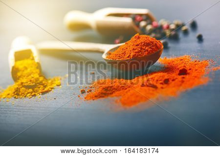 Colorful spices on a dark blue table. Concept of kitchen and cooking. Spicy on a wooden spoon.